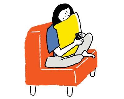 ソファでスマホをいじる女性